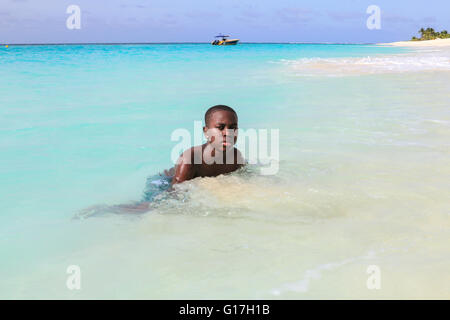 Local child swims at Shoal Bay in Anguilla - Stock Photo