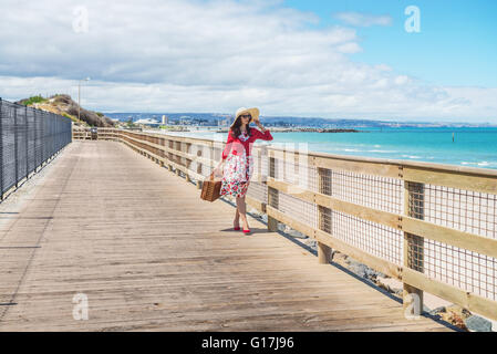 Adelaide seafront view and beautiful lady in red walking along wooden deck.Focus on the woman - Stock Photo