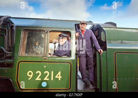 Driver and fireman on the footplate of an Ex-BR 9F freight locomotive 92214 on the West Somerset Railway, England, - Stock Photo