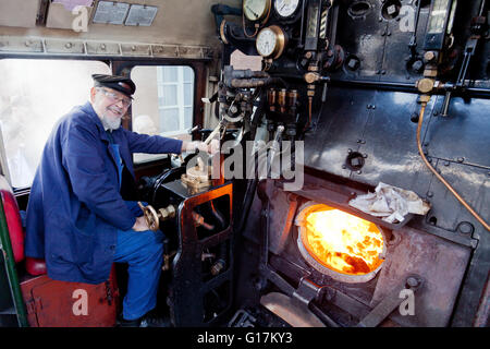 Driver Colin Henderson on the footplate of an Ex-BR 9F freight locomotive 92214 on the West Somerset Railway, England, - Stock Photo