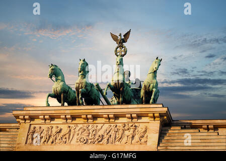 Quadriga and Bas-Relief on top of the Brandenburg Gate in Berlin, Germany with a sunset sky - Stock Photo