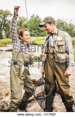 Man and woman standing in river wearing waders holding fishing rod smiling - Stock Photo