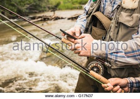 Cropped view of couple holding fishing rods and smartphone by river - Stock Photo