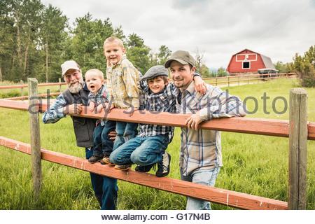 Multi generation family standing behind fence on farm looking at camera smiling - Stock Photo