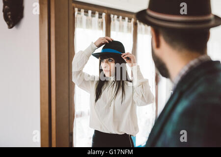 Young man waiting for woman trying on hat - Stock Photo
