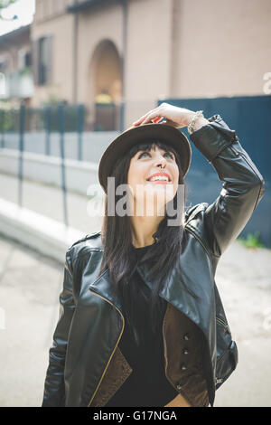 Happy young woman holding down hat - Stock Photo