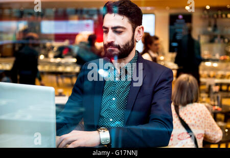 Businessman sitting in cafe window seat typing on laptop - Stock Photo