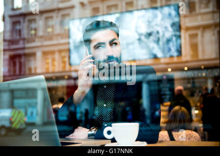 Businessman sitting in cafe window seat using laptop and smartphone - Stock Photo