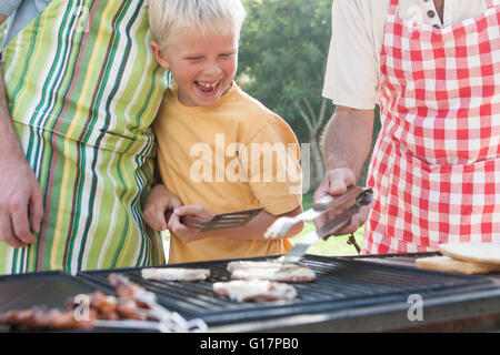 Boy cooking kebabs and burgers on barbecue with father and grandfather - Stock Photo