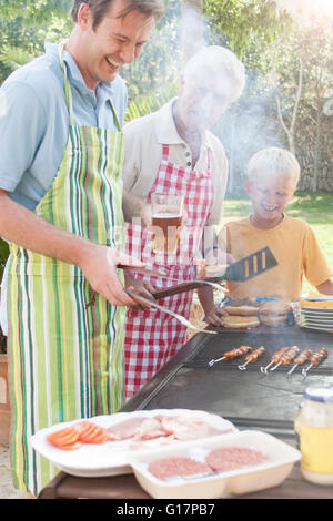 Family cooking kebabs and burgers on barbecue - Stock Photo