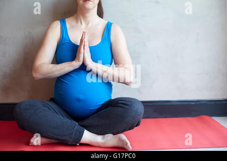 Pregnant woman sitting cross legged, hands together in yoga pose - Stock Photo