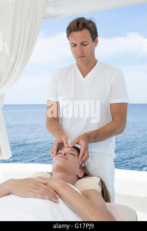 Male masseur giving young woman a head massage at beach resort, Majorca, Spain - Stock Photo