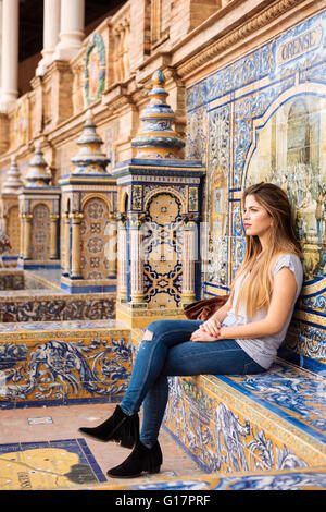 Young woman sitting relaxing at Plaza de Espana, Seville, Andalucia, Spain - Stock Photo