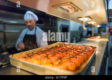 Chef cooking tomatoes in traditional Italian restaurant kitchen - Stock Photo
