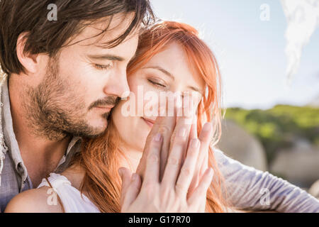 Head and shoulders of couple sitting hugging holding hands lovingly - Stock Photo