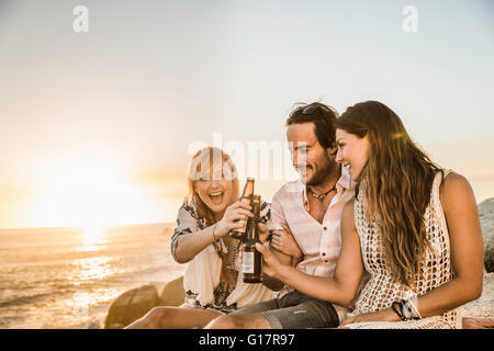 Three mid adult friends sitting on beach at sunset raising a toast, Cape Town, South Africa - Stock Photo