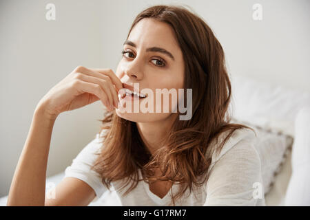 Portrait of beautiful young woman sitting on bed - Stock Photo