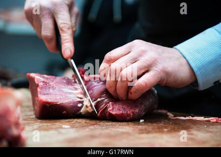Butcher preparing meat in butcher's shop, close-up - Stock Photo