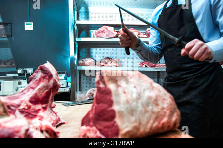 Butcher sharpening knife on knife steel in butcher's shop, mid section - Stock Photo