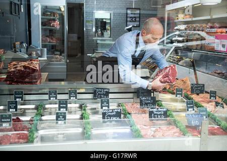 Butcher preparing window display in butcher's shop - Stock Photo
