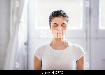 Young woman meditating with eyes closed in apartment - Stock Photo