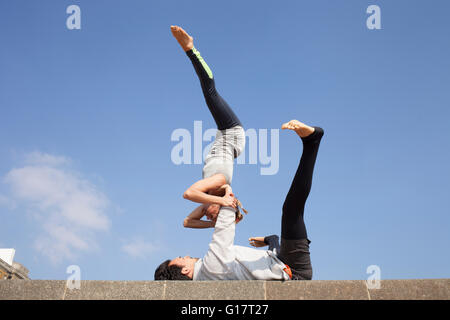 Man and woman practicing acrobatic yoga against blue sky