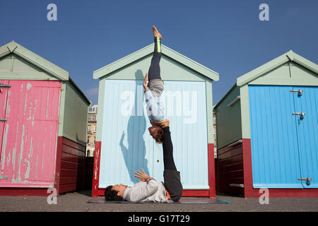 Man and woman practicing acrobatic yoga in front of beach huts at Brighton beach - Stock Photo