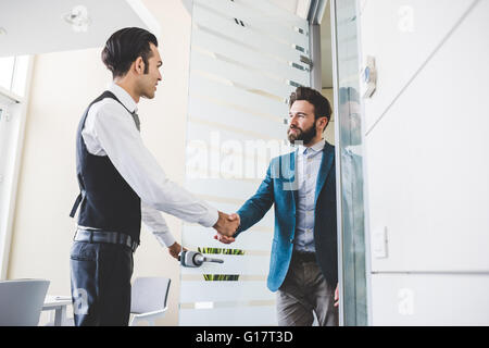 Young businessman and client shaking hands in office - Stock Photo