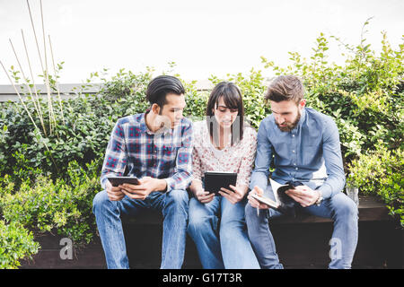 Three designers chatting on office roof terrace - Stock Photo