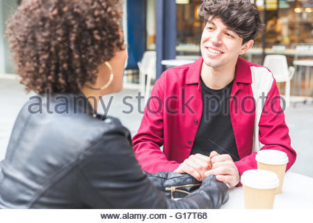Couple at sidewalk cafe with disposable cups, holding hands smiling - Stock Photo