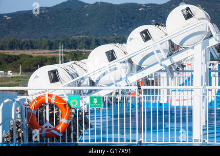 Inflatable liferafts in hard-shelled white containers and red lifebuoy hanging on railings. Modern passenger ship - Stock Photo