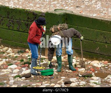 A couple searching for treasure using a metal detector on Hunstanton beach Norfolk England UK - Stock Photo