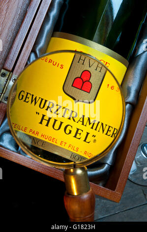 Magnifying glass with detail on bottle label of Alsace 'Hugel' Gewurztraminer white wine in presentation box - Stock Photo