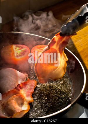 BACK BACON FRYING Shaft of sunlight illuminates a rasher of organic back bacon being turned in a hot frying pan - Stock Photo