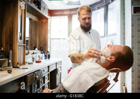 Hair mustache beard treatment in barber shop - Stock Photo