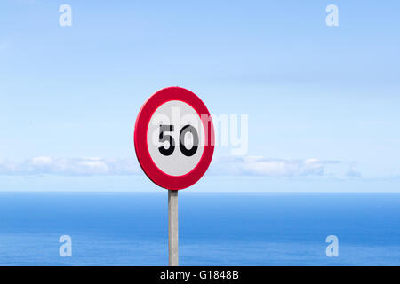 Fifty traffic sign. 50 miles per hour speed limit sign round red against blue sky - Stock Photo