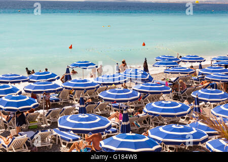 Baie Des Anges and blue sun umbrellas on beach, Nice, Cote D'Azur, France - Stock Photo