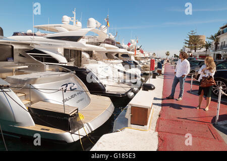 people looking at expensive boats and motor cruisers, Puerto Banus Harbour, Costa del Sol, Marbella Andalusia Spain - Stock Photo