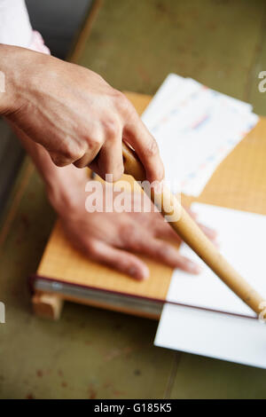 High angle view of mans hands using guillotine - Stock Photo