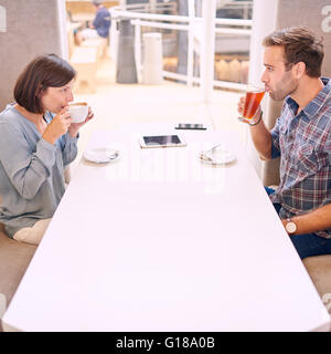 Couple looking at each other as they take their first sip on their first date after meeting online through a dating - Stock Photo