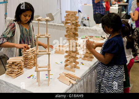 Girls stacking wooden toy blocks at science fair - USA - Stock Photo