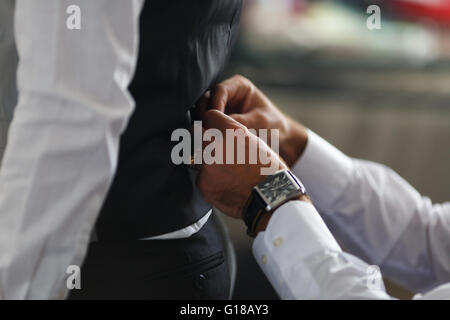 groom putting on cuff-links as he gets dressed in formal wear close up, close up of a hand man how wears white shirt - Stock Photo