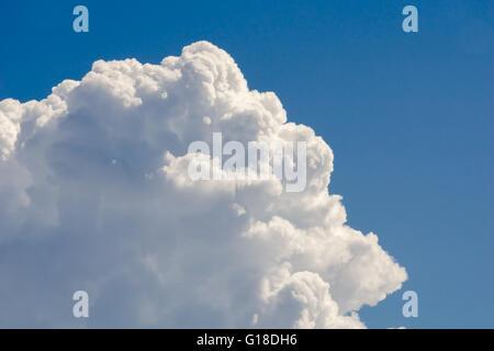 Big white cloud against bright blue sky - Stock Photo