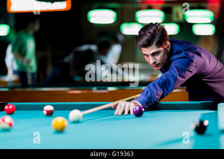 Young handsome man leaning over the table while playing snooker - Stock Photo