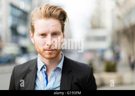Businessman portrait with blurred out city buildings in the background - Stock Photo