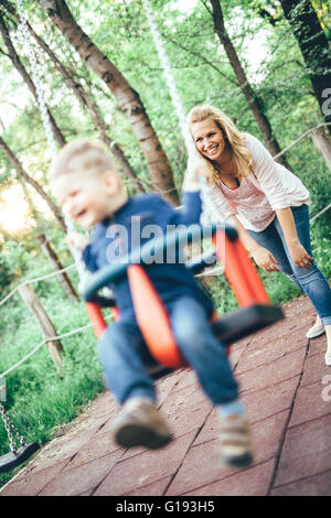 Mother and child outdoors in playground riding a  swing and smiling - Stock Photo