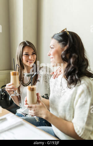 Two beautiful girls drinking coffee and smiling at their favorite bar - Stock Photo