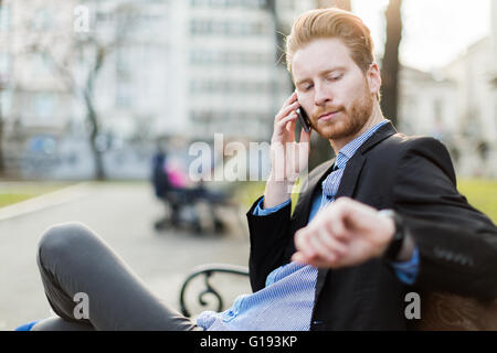 Businessman looking at his wrist watch on a sunny day in a city park - Stock Photo