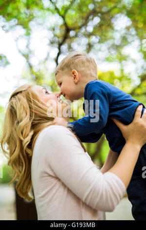 Beautiful young mother playing with her little son - Stock Photo
