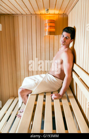 Handsome man relaxing in a sauna with towel wrapped around his waist - Stock Photo